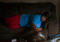 After a long day of work, an exhausted Janice Hensley lays on the couch while feeding her granddaughter, Faith, in her apartment Tuesday, May 12, 2015 in northeast Dallas. Hensley and her family have been living in their new apartment for a few weeks after spending more than a year at a homeless shelter. <i>I spent about a year covering Janice and her family as they tried to transition from a homeless shelter to a place of their own. The level of access, trust and kindness they showed me is something I'll never forget.</i>(G.J. McCarthy/Staff Photographer)