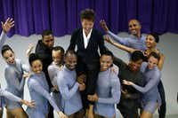 NEA chairman Jane Chu laughs as she is picked up for a photo with the Dallas Black Dance Theatre team in their practice theater in Dallas (Nathan Hunsinger/Staff Photographer)
