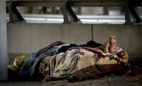 A man lays on a cot alongside I-45 near a homeless encampment. ((G.J, McCarthy/Staff Photographer))