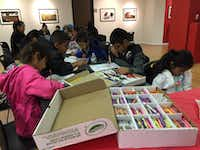 Children color at the Mexican consulate in Dallas, while their parents listen to presentations by Mexican and Dallas officials on potential policy changes with the Trump administration. (Ana Azpurua/Staff)