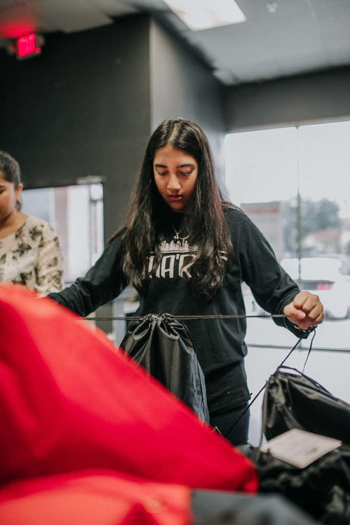 Saher Sayed, 15 packs a survival kit for the homeless in Dallas on an overcast Saturday. The packets include bottled water, socks, deodorant, toothpaste, a toothbrush, a washcloth and a blanket.Faiza M. Malik