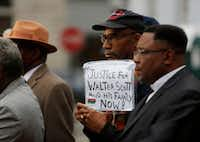 Dimitri Ford, from North Charleston, holds a sign supporting the Scott family during a prayer vigil in front of the Charleston County Courthouse as the jury deliberates in the Michael Slager trial Monday, Dec. 5, 2016, in Charleston, S.C. Slager, the former North Charleston police officer is charged with murder in the shooting death last year of Walter Scott. (AP Photo/Mic Smith)(AP)