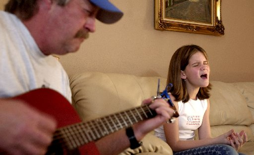 At 11 years old, Maren  Morris (right) practices her country songs with accompanist Randy Langley (left) at Morris' Grand Prairie home.