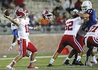 Evangel Christian Academy quarterback Connor Curry (left) threw a pass as the helmet of Evangel'€™s Tanner Coleman (62) appeared to float in the air after popping off as he blocked Allen's Peter Nicklas during a game at Eagle Stadium in Allen on Sept. 2. Allen won the game 45-10.(Jae S. Lee)