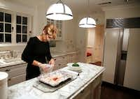 Laura Miller prepares dinner for her family in her kitchen. (David Woo/The Dallas Morning News)