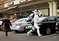 Taylor Wren, dressed as a storm trooper, raced across a strip shopping center parking lot as he was running late to a group photo outside the Alamo Draft House in Richardson on the opening day for Star Wars: The Force Awakens on Dec. 17, 2015. He was hurried along by David Petty (left).(Tom Fox)