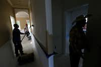 <p>Santos Coria (right) gave a tour of one of his houses in West Dallas as workers painted the walls on Oct. 6.</p>((Nathan Hunsinger/Staff Photographer))