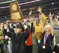 Cedar Hill head coach Joey McGuire hoists the UIL trophy after their 34-24 win for the state title during the Cedar Hill High School Longhorns vs. the Katy High School Tigers Class 5A Division II state title game at AT&T Stadium in Arlington on Saturday, December 21, 2013. (Louis DeLuca/Staff Photographer)