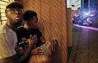 A man and boy took cover as shots were fired in this frame grab from a video taken during the July 7 police ambush.(G.J. McCarthy)