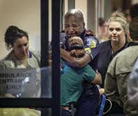 A Dallas Area Rapid Transit police officer was comforted at the Baylor University Hospital emergency room entrance on July 7. One of his colleagues on the DART police force, 43-year-old Officer Brent Thompson, was among those killed in the ambush. Thompson, a former Marine who had been with the department since 2009, was the first DART officer to be killed in the line of duty.(Ting Shen)