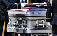 The colors of the Stars and Stripes were reflected on the surface of the coffin as the Arlington police honor guard prepared to fold the flag over the casket of DART Officer Brent Thompson during a memorial service at The Potter's House in Dallas on July 13. Thompson was one of five officers killed in the July 7 ambush.(Vernon Bryant)