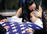 Kristy Villasenor, partner of Dallas police Officer Patrick Zamarripa, comforted her son, Dylan Hoover, after a funeral for the fallen officer on July 16 at Wilkerson-Greines Athletic Center in Fort Worth. Dylan is Zamarripa's stepson.(Ashley Landis)