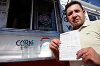 "Carlos Zamora shows a voter registration card from a pile placed on the counter of the Tierra Caliente taco truck on Sept. 29, 2016, in Houston. Zamora is with Mi Familia Vota, a Latino activist group that seeks to register more voters in the Latino community. Mi Familia Vota partnered with a local design firm to make eight of the city's taco trucks into mobile voter registration booths after a surrogate of Republican presidential candidate Donald Trump recently suggested that unless the United States fortifies its borders and tightens immigration limits, ""You're going to have taco trucks on every corner."" (John L. Mone/The Associated Press)"