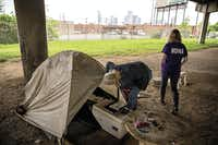 On April 19, Cindy Crain (left) and Rebecca Cox of the Metro Dallas Homeless Alliance sifted through belongings left in an abandoned section of the Tent City homeless camp in Dallas.(G.J. McCarthy)
