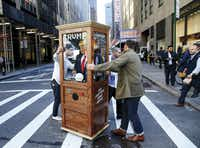 Artist Nathaniel Lawlor got some help from friend Jason Goodman as they pushed a fortune teller machine bearing Donald Trump'€™s image outside the Midtown Hilton in New York City on Nov. 8, 2016. When the red button is pushed, Trump's voice recites some of his famous and funny lines.(Tom Fox)