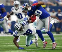 The Cowboys' Brandon Carr brought down Giants receiver Victor Cruz (80) after Cruz hauled in a pass from Eli Manning during the first Cowboys-Giants game of the seaon in September. (File Photo/Staff)
