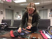 Cufflinks Inc. co-president Patty Bentley arranges Harry Potter men's and boy's accessories at the company's headquarters in Dallas. These ties and cufflinks came out for the 2016 release of the Fantastic Beasts and Where to Find Them.(DMN Staff Maria Halkias)