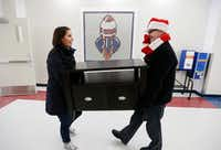 Hayley Heider (left) and Dave Rogers of Looney and Associates carry in a table for a nearly decorated teachers lounge at J.W. Ray Elementary School in Dallas, Thursday, December 8, 2016. The interior design firm raised money and donations to help redecorate two teacher lounges, provide a new laundry washer and dryer, school supplies and sports equipment. (Brandon Wade/Special Contributor)
