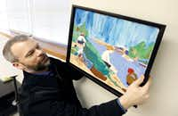 Brian Belcher, with Looney and Associates, hangs a student's artwork in a nearly decorated teachers lounge at JW Ray Elementary School in Dallas.(Brandon Wade/Special Contributor)