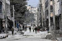 This photo released by the Syrian official news agency SANA, shows Syrian soldiers and civilians marching through the streets of east Aleppo, Syria, Monday, Dec. 12, 2016. (SANA via AP)(AP)
