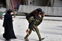 In this photo released by the Syrian official news agency SANA, a Syrian soldier carries a wounded woman in eastern Aleppo, Syria, Monday, Dec. 12, 2016. (SANA via AP)(AP)