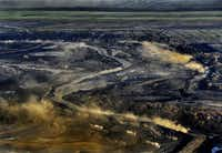 Dust rises from the Alberta, Canada, oil sands project of Syncrude, which is partly owned by Imperial, Exxon's Canadian affiliate.((2012 File Photo/Michael Williamson/The Washington Post))