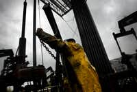2005 FILE PHOTO -- Junior Floor Hand Mason Mack takes care of maintenance on an oil derrick at Imperial Oil Ltd.'s Cold Lake project in Alberta, Canada.(Lara Solt/Staff photographer)