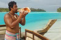 Guide Ali Maao blows a conch shell to signal the tour boat s departure from One Foot Island during a half-day cruise of Aitutaki's blue lagoons.(Jay Jones)