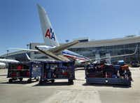 American Airlines luggage sits on the tarmac outside of Terminal D at Dallas/Fort Worth International Airport, Tuesday, June 11, 2014.  (Tom Fox/The Dallas Morning News)(Staff Photographer)