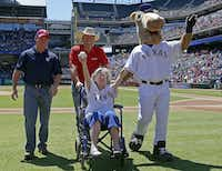 Elizabeth Sullivan, 105-years-old from Fort Worth, on a wheelchair, waves to the crowd as she wheels off with Kirk Conger, of Dr. Pepper, left, Chad Prather, center, and Rangers Captain after she throws out the ceremonial first pitch at the Rangers and Mariners game at Globe Life Park in Arlington, Texas, Wednesday, April 6, 2016. (Jae S. Lee/The Dallas Morning News)(Jae S. Lee/Staff Photographer)