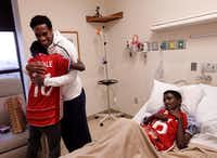Markos Bogale (left), 16, hugs FC Dallas player Atiba Harris as Tamirat Bogale, 16, watches during a visit at Medical Center of Plano. (Jason Janik/Special Contributor)