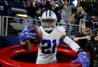 Ezekiel Elliott #21 of the Dallas Cowboys celebrates after scoring a touchdown by jumping into a Salvation Army red kettle during the second quarter against the Tampa Bay Buccaneers at AT&T Stadium on December 18, 2016 in Arlington, Texas.  (Photo by Tom Pennington/Getty Images)(<br>)