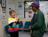 Sims greets Ralphford Leach as he comes into the food bank. (Nathan Hunsinger/Staff Photographer)