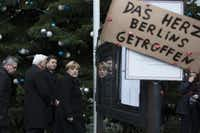 "Angela Merkel, Germany's chancellor, center, Thomas de Maiziere, Germany's interior minister, left, Frank-Walter Steinmeier, Germany's foreign minister, second left, and Andreas Geisel, Berlin's interior minister, visit the scene of yesterday's terror attack as a handwritten sign reading ""the heart of Berlin is hit"" sits on display in Berlin, Germany, on Tuesday, Dec. 20, 2016.(Bloomberg)"
