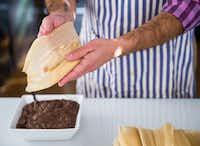 Eddie Garza makes vegan black bean tamales.(Ashley Landis/ The Dallas Morning News)