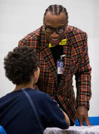 Dallas County Commissioner John Wiley Price talks with a juvenile inmate on the day the youth and others receive donated Christmas gifts at the Jerome McNeil Juvenile Detention Center. (Ashley Landis/Staff Photographer)