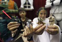 Pittsford,  N.Y.,  residents Chase Boss, left, 11, as Luke Skywalker and his twin sister, Sydney, as Princess Leia  hold Star Wars action figures, which were  inducted into the National Toy Hall of Fame at The Strong in Rochester, N.Y., on Nov. 15, 2012. (The Associated Press)