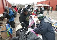 The homeless and needy looked through donated clothing as they attended the Christmas Day Banquet held by BIGHEART Ministries at the  Dallas International Street Church in South Dallas. (Rex C. Curry/Special Contributor)