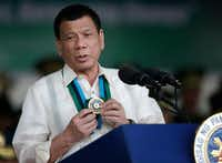 Philippine President Rodrigo Duterte shows a medal during his speech to troops during the 81st anniversary of the Armed Forces of the Philippines at Camp Aguinaldo military headquarters in Quezon city, north of Manila, Philippines on Wednesday, Dec. 21, 2016. (AP Photo/Aaron Favila)(AP)