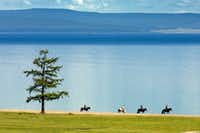 "Riders on horseback explore the edge of Lake Hovsgol, the largest freshwater lake Mongolia, with Nomadic Expeditions. <p><span style=""font-size: 1em; background-color: transparent;"">Nomadic Expeditions</span><br></p><p></p>"