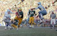 Green Bay Packers Jim Taylor runs with a Bart Starr pass as the Dallas Cowboys' Mel Renfro (20) leaps too late to break up the pass during the NFL Championship game, Jan. 1, 1967 in  Dallas.  At left is Cowboys Chuck Howley (54). ((File Photo/The Associated Press))