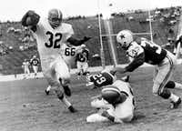 Jim Brown (32), fullback of the Cleveland Browns, appears at the Cotton Bowl, picking up a first down before being stopped by Tom Franckhauser (32). Cleveland won 48-7, in a game played on Oct. 16, 1960, during the Cowboys' first season. Notice the empty seats.((File Photo/The Associated Press))