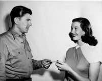 In this March 30, 1947 picture, Lois Maxwell, 20-year-old Canadian-born actress, receives her Screen Actors Guild member card from the new president of the guild, actor Ronald Reagan, in Hollywood, Calif. (AP Photo)(AP)