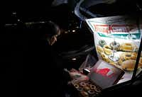 Sonia Garcia sells Krispy Kreme doughnuts, purchased across the border in El Paso, from the trunk of her car on a busy street in Ciudad Juarez, Mexico. The money she and her family make selling doughnuts helps pay for her son to go to college.<br>(Katie Falkenberg/Los Angeles Times/TNS)