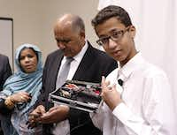 "Ahmed Mohamed, right, labeled ""Clock Boy"" shows the clock he built in a school pencil box while standing with his parents, Muna Ibrahim, left, and Mohamed Elhassan, after a news conference in Dallas, Monday, August 8, 2016. (David Woo/Staff Photographer)"