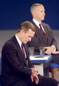 In a classic debate moment, President George H.W. Bush looks at his watch during a presidential debate at the University of Richmond in October 1992. Independent candidate Ross Perot is at right. Bush later lost the election to Bill Clinton.(Ron Edmonds/Associated Press)