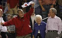 Former president George H.W. Bush waves a towel as wife Barbara and son George W. Bush look on during the World Series Game 4 between the Texas Rangers and San Francisco Giants at Rangers Ballpark in Arlington on Oct. 31, 2010.(Louis DeLuca/Staff Photographer)