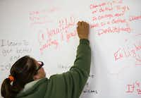 Frances Martinez writes a note on a whiteboard after a group session. (Ashley Landis/The Dallas Morning News)(Staff Photographer)