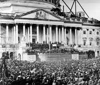 """In this March 4, 1861, file photo, U.S. President Abraham Lincoln stands under cover at center of Capitol steps during his inauguration. He passionately made the case against a civil war: """"We are not enemies, but friends. We must not be enemies.""""(AP)"""