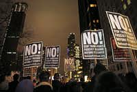 Protesters hold signs as they listen to speakers at an anti-Trump rally hosted by filmmaker Michael Moore in front of the Trump International Hotel, Thursday, Jan. 19, 2017, in New York. President-elect Donald Trump, a New Yorker, is scheduled to take the oath of office Friday in Washington.(Kathy Willens/AP)